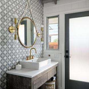 Réalisation d'un WC et toilettes marin de taille moyenne avec un placard à porte plane, des portes de placard en bois vieilli, un WC à poser, un carrelage gris, des carreaux de béton, un mur blanc, un sol en carreaux de ciment, un lavabo de ferme, un plan de toilette en quartz modifié, un sol gris, un plan de toilette blanc, meuble-lavabo sur pied, un plafond en poutres apparentes et du lambris.