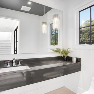 Medium sized coastal cloakroom in New York with a one-piece toilet, light hardwood flooring, a submerged sink, white walls, beige floors and grey worktops.