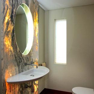 Immagine di un bagno di servizio di medie dimensioni con pistrelle in bianco e nero, piastrelle di marmo, pareti bianche, parquet scuro, lavabo sospeso e pavimento rosso