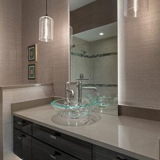 Imagen de aseo de estilo zen, de tamaño medio, con lavabo sobreencimera, armarios tipo mueble, puertas de armario de madera en tonos medios, baldosas y/o azulejos beige, suelo de baldosas de porcelana y sanitario de una pieza