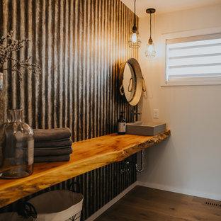 Inspiration pour un WC et toilettes design de taille moyenne avec un placard sans porte, des portes de placard en bois brun, un carrelage gris, carrelage en métal, un mur blanc, un sol en bois brun, une vasque, un plan de toilette en bois et un sol marron.