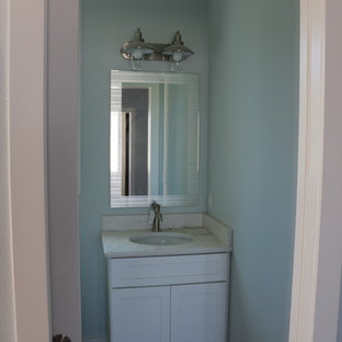 Example of a mid-sized beach style dark wood floor and brown floor powder room design in Orlando with shaker cabinets, white cabinets, blue walls, an undermount sink and quartzite countertops