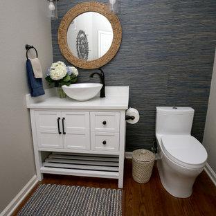 На фото: маленький туалет в морском стиле с фасадами с выступающей филенкой, белыми фасадами, унитазом-моноблоком, синей плиткой, синими стенами, темным паркетным полом, настольной раковиной, столешницей из искусственного кварца, коричневым полом и белой столешницей с