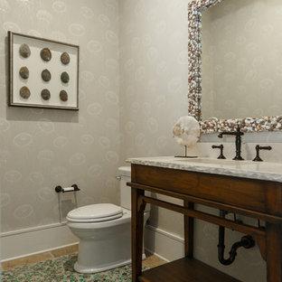 На фото: туалеты в морском стиле с фасадами островного типа, фасадами цвета дерева среднего тона, полом из керамогранита, врезной раковиной, столешницей из травертина и зеленым полом