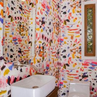 Ejemplo de aseo clásico, pequeño, con urinario, paredes rojas, suelo de cemento, lavabo con pedestal y suelo gris
