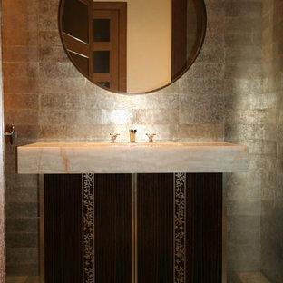 Imagen de aseo actual, de tamaño medio, con lavabo integrado, armarios tipo mueble, encimera de ónix, baldosas y/o azulejos grises y baldosas y/o azulejos de metal