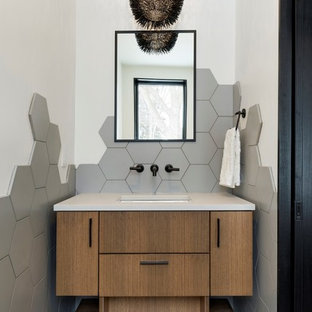 Example of a trendy gray tile gray floor powder room design in Minneapolis with flat-panel cabinets, medium tone wood cabinets, gray walls, an undermount sink and gray countertops