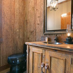 シアトルの大きいラスティックスタイルのおしゃれなトイレ・洗面所 (オーバーカウンターシンク、中間色木目調キャビネット、木製洗面台、一体型トイレ、スレートの床、落し込みパネル扉のキャビネット) の写真
