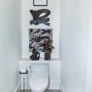 アトランタの小さいモダンスタイルのおしゃれなトイレ・洗面所 (フラットパネル扉のキャビネット、白いキャビネット、一体型トイレ、グレーのタイル、石スラブタイル、白い壁、磁器タイルの床、壁付け型シンク、珪岩の洗面台、グレーの床、グレーの洗面カウンター) の写真