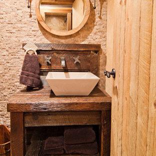 サクラメントのラスティックスタイルのおしゃれなトイレ・洗面所 (ベッセル式洗面器、オープンシェルフ、濃色木目調キャビネット、木製洗面台、ベージュのタイル、ブラウンの洗面カウンター) の写真