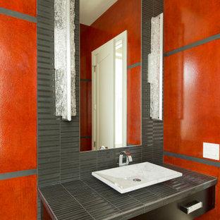 ポートランドの広いモダンスタイルのおしゃれなトイレ・洗面所 (フラットパネル扉のキャビネット、黒いキャビネット、一体型トイレ、赤いタイル、モザイクタイル、赤い壁、磁器タイルの床、ベッセル式洗面器、タイルの洗面台、白い床、グレーの洗面カウンター) の写真
