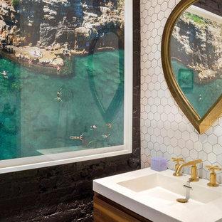 Cette image montre un petit WC et toilettes design avec un placard à porte plane, des portes de placard en bois brun, un carrelage blanc, des carreaux de porcelaine, un mur noir, un plan de toilette en surface solide et un plan vasque.