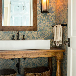 Example of a classic powder room design in New York with furniture-like cabinets, medium tone wood cabinets, multicolored walls, a vessel sink, wood countertops and brown countertops