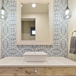 Стильный дизайн: туалет среднего размера в стиле кантри с фасадами островного типа, искусственно-состаренными фасадами, синей плиткой, цементной плиткой, белыми стенами, настольной раковиной и столешницей из кварцита - последний тренд