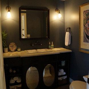 Klassische Gästetoilette mit verzierten Schränken, dunklen Holzschränken, Recyclingglas-Waschtisch, Wandtoilette mit Spülkasten, Porzellan-Bodenfliesen und blauer Wandfarbe in Los Angeles