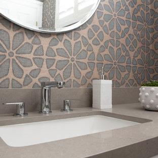 Inspiration pour un petit WC et toilettes design avec un placard avec porte à panneau surélevé, un WC à poser, un carrelage bleu, un mur bleu, un sol en carrelage de céramique, un lavabo encastré, un plan de toilette en quartz modifié, un sol gris et un plan de toilette gris.