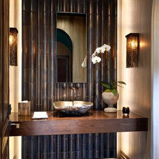 Foto på ett tropiskt toalett, med ett fristående handfat och träbänkskiva