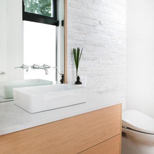 Стильный дизайн: туалет в современном стиле с плоскими фасадами, светлыми деревянными фасадами, унитазом-моноблоком, каменной плиткой, белыми стенами, настольной раковиной, столешницей из кварцита, белой плиткой, светлым паркетным полом, белой столешницей и подвесной тумбой - последний тренд