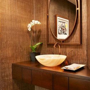 Стильный дизайн: маленький туалет в современном стиле с плоскими фасадами, фасадами цвета дерева среднего тона, унитазом-моноблоком, коричневой плиткой, коричневыми стенами, мраморным полом, настольной раковиной, столешницей из дерева и коричневой столешницей - последний тренд