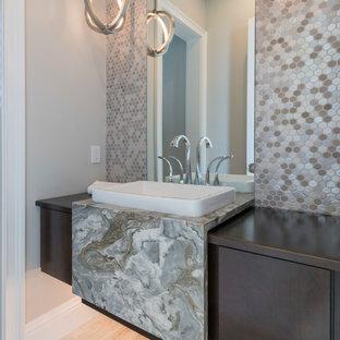 Exemple d'un WC et toilettes tendance avec un placard à porte plane, des portes de placard en bois sombre, carrelage en mosaïque, un mur beige, un sol en bois clair, un plan de toilette en marbre et un plan de toilette gris.