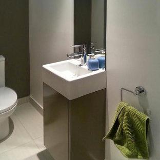На фото: маленький туалет в современном стиле с плоскими фасадами, бежевыми фасадами, керамической плиткой, белыми стенами, полом из керамической плитки, столешницей из искусственного камня, раздельным унитазом и подвесной раковиной с