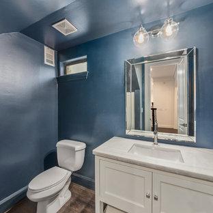 Kleine Klassische Gästetoilette mit Schrankfronten mit vertiefter Füllung, weißen Schränken, Quarzit-Waschtisch, weißer Waschtischplatte, Toilette mit Aufsatzspülkasten, blauer Wandfarbe, Laminat, Unterbauwaschbecken und braunem Boden in Houston