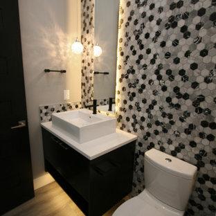 Foto di un bagno di servizio minimal di medie dimensioni con ante lisce, ante nere, WC monopezzo, pistrelle in bianco e nero, piastrelle in pietra, pareti grigie, pavimento in vinile, lavabo a bacinella, top in quarzo composito, pavimento grigio e top bianco
