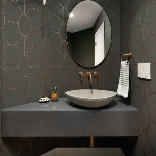 На фото: туалеты в современном стиле с серыми стенами, паркетным полом среднего тона, настольной раковиной, коричневым полом и серой столешницей