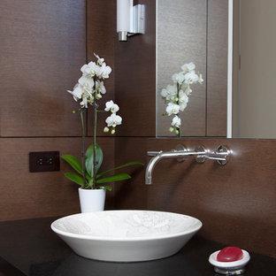 Imagen de aseo actual con lavabo sobreencimera, encimera de granito y encimeras negras