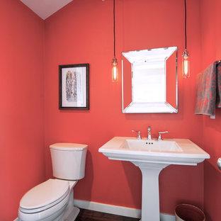 Bild på ett vintage toalett, med röda väggar, mörkt trägolv och brunt golv