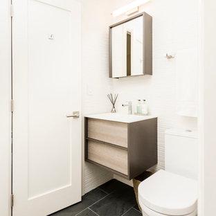 Idées déco pour un WC et toilettes contemporain de taille moyenne avec des portes de placard en bois clair, un WC à poser, un carrelage blanc, un mur blanc, un sol en carrelage de céramique, un lavabo posé, un plan de toilette en surface solide, un sol noir, un placard à porte plane, un carrelage de pierre et un plan de toilette blanc.