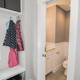 Photo of a small traditional cloakroom in Boston with shaker cabinets, white cabinets, a two-piece toilet, multi-coloured tiles, grey walls, porcelain flooring, a submerged sink and quartz worktops.