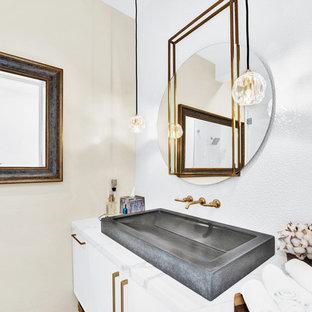 На фото: маленький туалет в современном стиле с фасадами в стиле шейкер, белыми фасадами, бежевыми стенами, раковиной с несколькими смесителями, столешницей из кварцита и белой столешницей