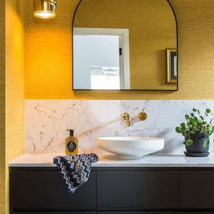 Cette photo montre un WC et toilettes tendance de taille moyenne avec un placard en trompe-l'oeil, des portes de placard noires, un WC suspendu, un carrelage bleu, des carreaux de porcelaine, un mur jaune, un sol en carreaux de ciment, une vasque, un plan de toilette en quartz modifié, un sol gris, un plan de toilette blanc, meuble-lavabo encastré, un plafond décaissé et du papier peint.
