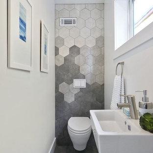 Diseño de aseo minimalista, pequeño, con sanitario de una pieza, baldosas y/o azulejos grises, baldosas y/o azulejos de pizarra, paredes grises y lavabo sobreencimera