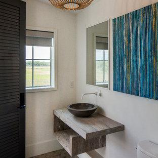 На фото: туалеты в стиле кантри с открытыми фасадами, раздельным унитазом, белыми стенами, полом из мозаичной плитки, настольной раковиной, столешницей из дерева, разноцветным полом и коричневой столешницей