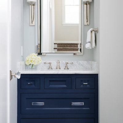 Example of a small transitional dark wood floor and brown floor powder room design in DC Metro with recessed-panel cabinets, blue cabinets, beige walls, an undermount sink, marble countertops and gray countertops
