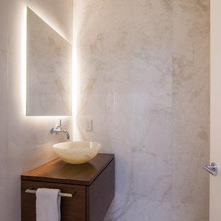 Неиссякаемый источник вдохновения для домашнего уюта: туалет среднего размера в современном стиле с плоскими фасадами, темными деревянными фасадами, бежевой плиткой, бежевыми стенами, полом из известняка, настольной раковиной, столешницей из дерева, бежевым полом и коричневой столешницей