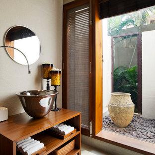Foto de aseo exótico con armarios abiertos, puertas de armario de madera oscura, paredes beige, lavabo sobreencimera, encimera de madera y encimeras marrones