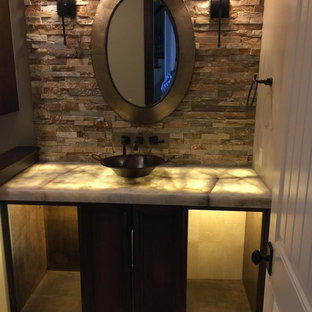 This is an example of a small traditional cloakroom in Other with flat-panel cabinets, black cabinets, red tiles, stone tiles, beige walls, travertine flooring, a vessel sink, onyx worktops and beige floors.