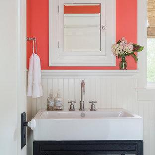 ロサンゼルスの広いトラディショナルスタイルのおしゃれなトイレ・洗面所 (家具調キャビネット、ピンクの壁、コンソール型シンク、黒いキャビネット) の写真