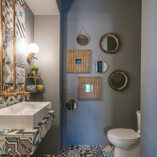 Cette image montre un WC et toilettes design avec un carrelage multicolore, un mur gris, une vasque, un plan de toilette en carrelage, un sol multicolore et un plan de toilette multicolore.