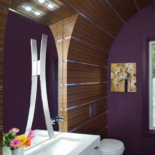 На фото: туалет среднего размера в современном стиле с врезной раковиной, плоскими фасадами, белыми фасадами, столешницей из искусственного кварца, инсталляцией, фиолетовыми стенами, полом из керамогранита и белой столешницей