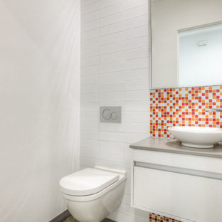 Small modern cloakroom in Houston with flat-panel cabinets, white cabinets, multi-coloured tiles, mosaic tiles, white walls, travertine flooring, solid surface worktops, beige floors, a wall mounted toilet and a vessel sink.