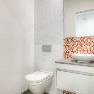 Идея дизайна: маленький туалет в стиле модернизм с плоскими фасадами, белыми фасадами, разноцветной плиткой, плиткой мозаикой, белыми стенами, полом из травертина, столешницей из искусственного камня, бежевым полом, инсталляцией и настольной раковиной