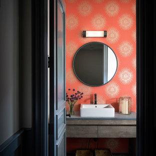Idée de décoration pour un petit WC et toilettes tradition avec un placard à porte plane, des portes de placard en bois sombre, un mur orange, un sol en bois foncé, une vasque, un sol marron et un plan de toilette gris.