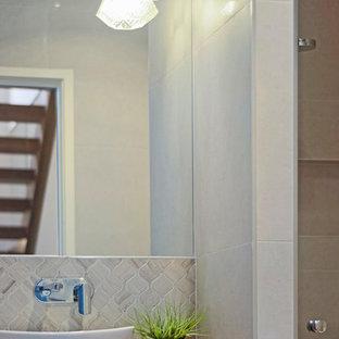 Immagine di un piccolo bagno di servizio design con consolle stile comò, ante in legno scuro, WC sospeso, piastrelle a mosaico, pavimento in gres porcellanato, lavabo a bacinella e top in laminato