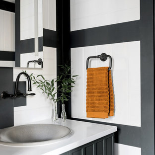 シカゴの小さいモダンスタイルのおしゃれなトイレ・洗面所 (レイズドパネル扉のキャビネット、黒いキャビネット、一体型トイレ、白い壁、竹フローリング、オーバーカウンターシンク、珪岩の洗面台、茶色い床、白い洗面カウンター) の写真