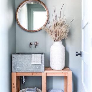 ポートランド(メイン)の小さいビーチスタイルのおしゃれなトイレ・洗面所 (家具調キャビネット、中間色木目調キャビネット、グレーの壁、スレートの床、ソープストーンの洗面台、グレーの床、グレーの洗面カウンター) の写真