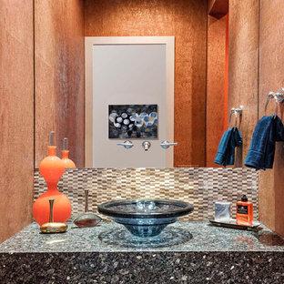 Imagen de aseo minimalista, de tamaño medio, con parades naranjas, suelo de madera clara, lavabo sobreencimera, encimera de granito, suelo marrón y encimeras negras